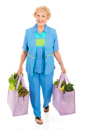 body bag: Beautiful senior lady carries her groceries in reusable cloth bags.  Full body isolated.   Stock Photo