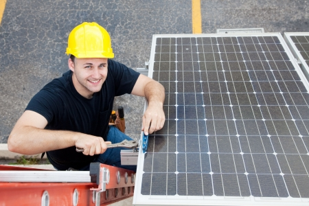 journeyman: Electrician installing solar panels on the roof of a building.