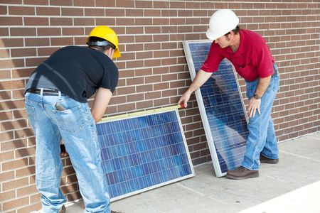 them: Electricians measuring solar panels prior to installing them.