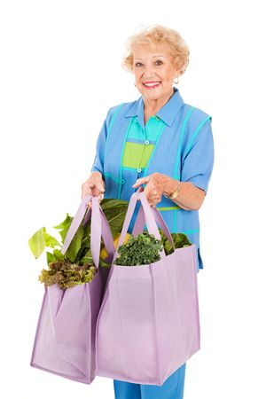 global retirement: Senior woman carrying her groceries in reusable cloth grocery bags.  Isolated on white.