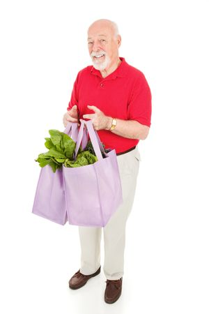 Healthy senior man brings home groceries in reusable cloth shopping bags.  Isolated on white. Stock fotó