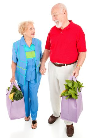 Senior couple walking home with their groceries in reusable shopping bags.  Isolated on white. Stock Photo - 4856268