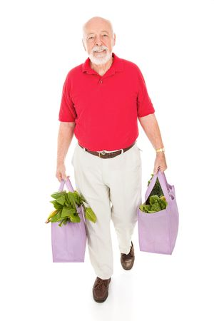 global retirement: Senior man carries his groceries home in reusable cloth shopping bags.  Full body isolated. Stock Photo
