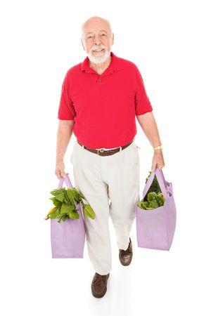 reusable: Senior uomo esercita la sua casa in drogheria stoffa borse della spesa riutilizzabili. Corpo pieno isolati. Archivio Fotografico