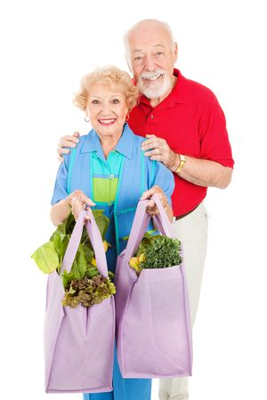Senior couple using reusable shopping bags to bring home their groceries.  Isolated on white.   photo