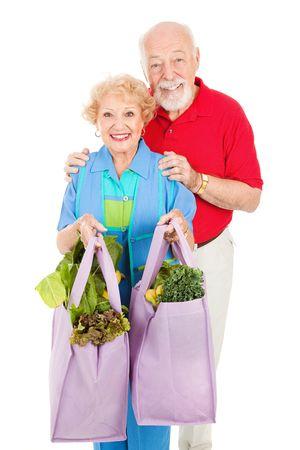 apporter: Senior couple utilisant des sacs de caisse r�utilisables � la maison de leur �picerie. Isolated on white.
