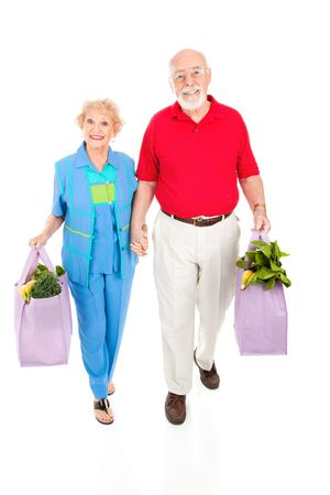 global retirement: Environmentally aware senior couple bringing home groceries in reusable bags.  Isolated on white. Stock Photo