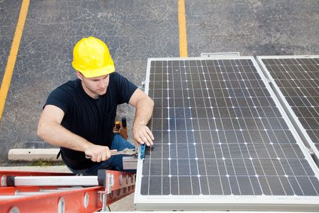 panel: Electrician repairing solar panel.  Wide angle view with room for text. Stock Photo
