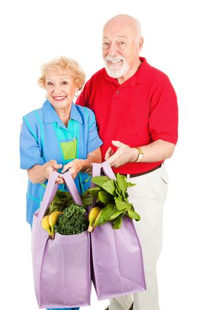 global retirement: Environmentally conscious senior couple uses reusable grocery bags.  Isolated on white.