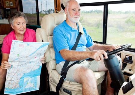 Senior couple on vacation in their motor home.  The wife is reading the map to her husband. photo