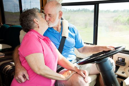 distracted: Vacationing senior couple kissing while he is driving their motor home.   Stock Photo