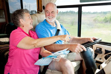 Senior couple on vacation in their motor home.  The wife is reading the map for the husband. photo