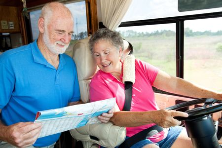 Senior couple in their motor home consulting a map.   photo
