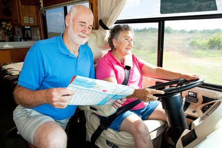 Senior couple on the road in their RV.  The wife is driving while the husband reads the map. photo