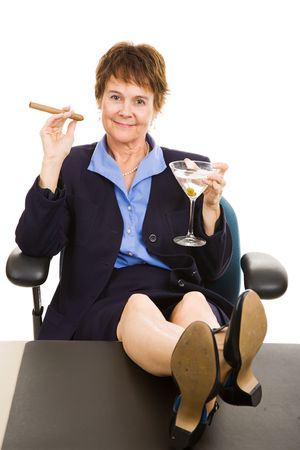 Mature businesswoman celebrates success with her feet on her desk as she enjoys a cigar and a martini. Stock Photo - 4893885