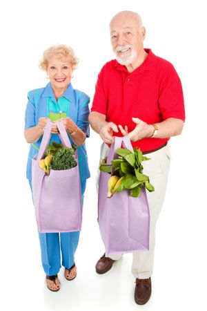 Senior couple bringing home fresh produce in reusable cloth grocery bags.  Full body isolated on white. Stock Photo - 4893879
