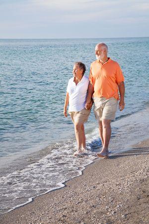 financially: Retired senior couple takes a romantic stroll on the beach.   Stock Photo