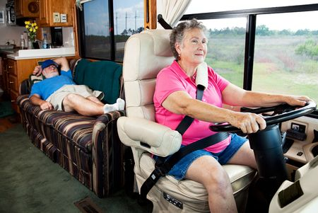 Senior woman driving the motor home on vacation while her husband sleeps in the back.   photo