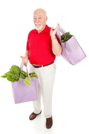 reusable: Handsome senior man shops for organic produce using reusable cloth grocery bags.  Isolated on white.