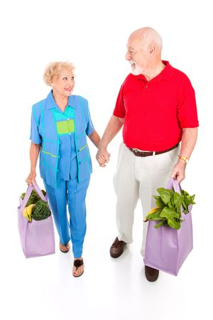 Senior couple returns from grocery shopping.  Full body isolated on white. photo