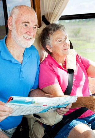 Senior couple reading a map and traveling in their motor home.   photo