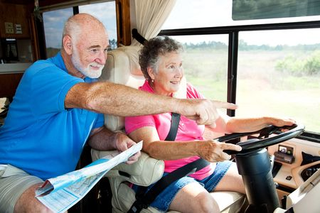 Senior couple traveling in their motor home.  The husband is giving directions to the wife.   Stock Photo