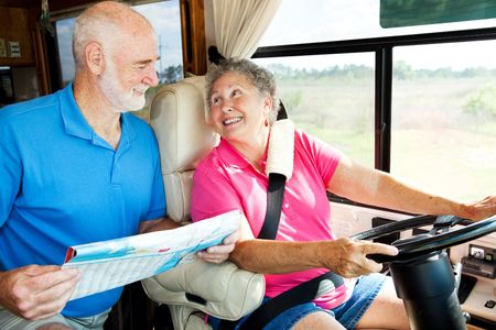 Senior couple riding in their motor home consult a map.   photo