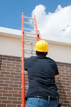 ladder safety: Construction worker using a ladder to climb to the top of a building.