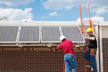 room for text: Workers installing solar panels on the side of a building.  Wide angle view with room for text.