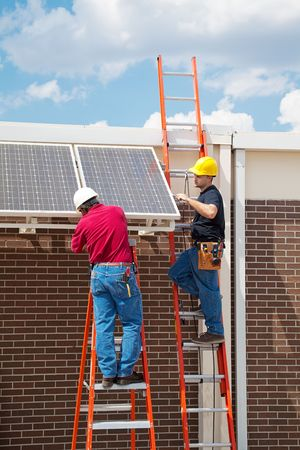 journeyman: Two workers installing solar panels on the side of a building.  Vertical with room for text.