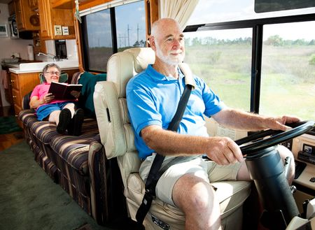 Retired senior couple traveling by motor home.  The husband drives while the wife reads in back. photo