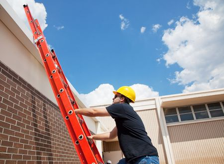 ladder safety: Construction worker climbing up to the roof of a building.  Wide view with lots of room for text.   Stock Photo