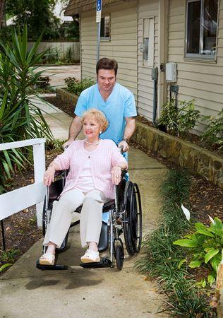 ordelijk: Senior vrouw aankomt op een verpleeghuis en is wielen binnen door een vriendelijke ordelijk. Stockfoto