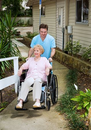 arrives: Senior woman arrives at a nursing home and is wheeled inside by a friendly orderly. Stock Photo