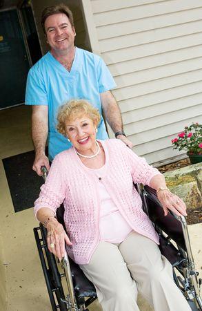 ordelijk: Happy senior vrouw in een verpleeghuis, verzorgd door een vriendelijke ordelijk. Stockfoto