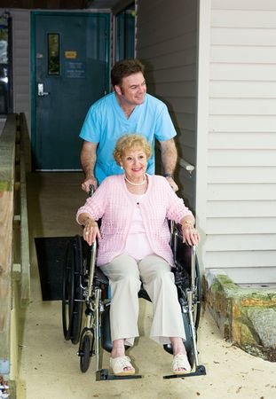 on ramp: Orderly takes a disabled senior woman out for a walk.