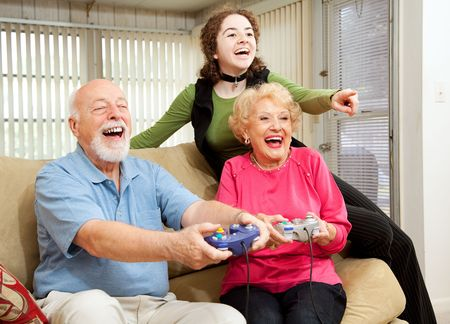 playing video games: Grandparents and teen girl having fun playing video games.