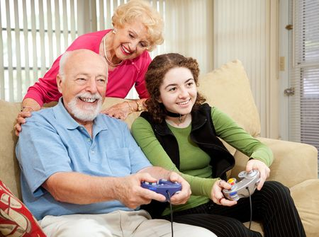 granny: Senior couple has fun playing video games with their teenage granddaughter. Stock Photo