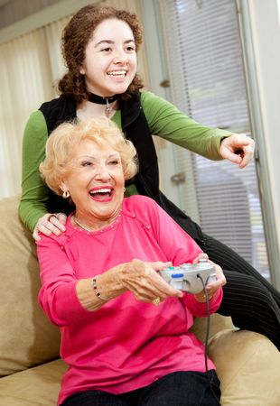 seventy two: Grandmother and teen granddaughter having a great time playing video games.