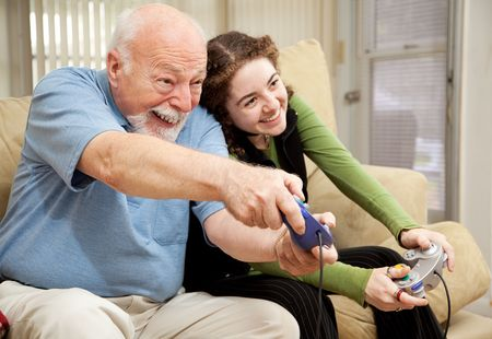 Grandfather enjoys playing video games with his teenage granddaughter. 免版税图像
