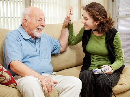 Teen girl playing video games, getting a high five from her grandfather. photo