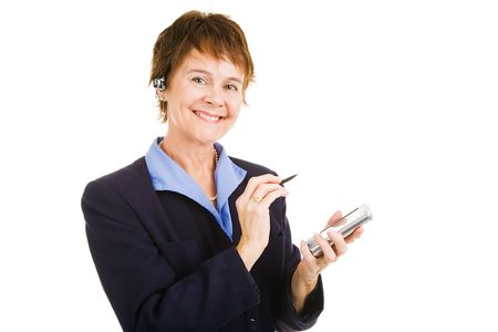 earpiece: Mature businesswoman with her personal organizer and her hands free telephone earpiece.  Isolated Stock Photo