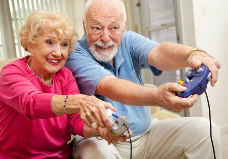 video gaming: Senior couple having fun playing video games.