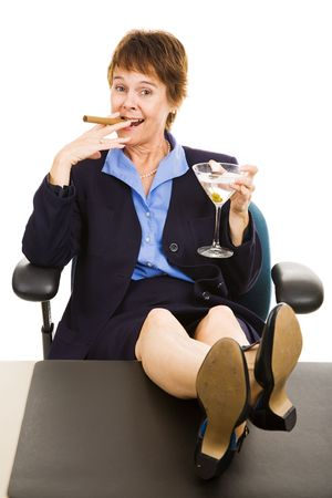 Successful business woman relaxing with a cocktail and a cigar.  Isolated. photo
