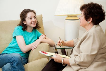 social worker: Woman interviewing a teen girl for college admission or job.  Could also be counseling session. Stock Photo