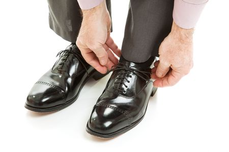 formal attire: Man ties his shiney new black leather business shoes.  Isolated on white.