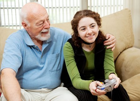 seventy two: Grandfather watching teen granddaughter play video games.
