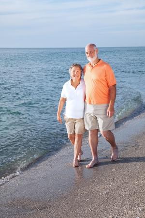 stroll: Happy senior couple take a stroll on a beautiful tropical beach. Stock Photo