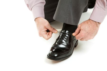 Mans hands tying shoelace of his new oxford shoes.  Isolated on white. photo