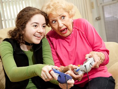 Grandmother and granddaughter playing an exciting video game together.   photo